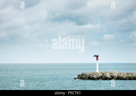 Solar powered Navigation beacon and man made harbour wall, Dunkirk, France, Europe - Stock Photo