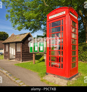 Traditional British red phone box, bus shelter and village notice board scene at Lurgashall, West Sussex, England, UK - Stock Photo