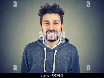 Closeup of happy bearded handsome man blue hoodie smiling cheerfully at camera on gray background - Stock Photo
