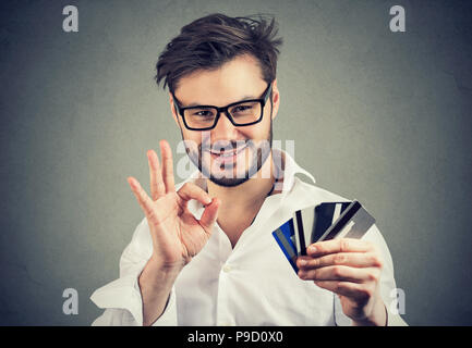 Content businessman in glasses holding pile of credit cards and showing OK gesture approving bank choice - Stock Photo