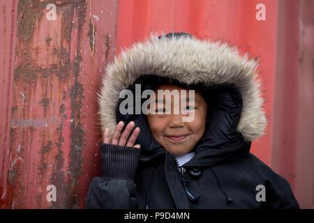 Canada, Nunavut, western shore of Hudson Bay, Kivalliq Region, Arviat. Young boy waving. - Stock Photo