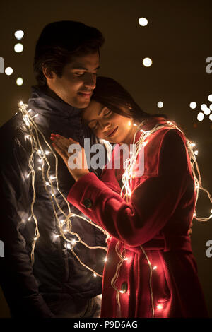 Romantic young couple wrapped in decorative lights - Stock Photo