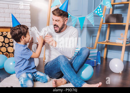 Cheerful bearded male person playing with son - Stock Photo