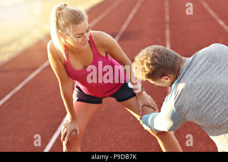 Man and woman racing on outdoor track - Stock Photo
