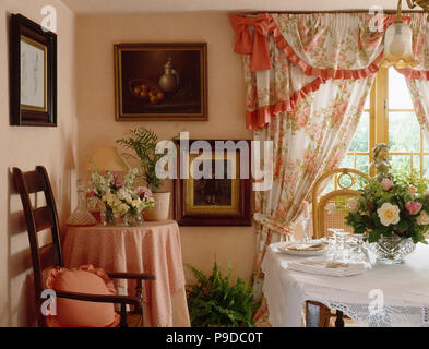 Floral curtains edged with peach trim in nineties dining room with white cloth on table - Stock Photo