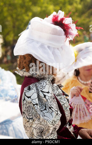 Elderly lady wearing a medieval formal dress and a hat. Mysterious old woman hiding her face. Historical female costume in a role-play - Stock Photo