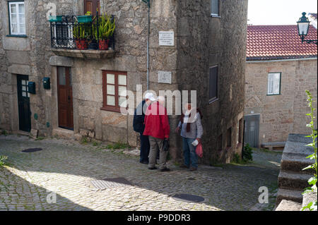 12.06.2018, Monsanto, Portugal, Europe - Three elderly men are seen having a chat in front of a residential house in the mountain village of Monsanto. - Stock Photo