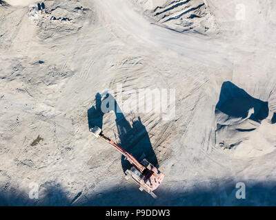 An aerial shot looking straight down at an orange digger in a quarry, Wales, UK - Stock Photo