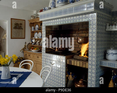 Lighted fire in tiled fireplace in eighties kitchen dining room - Stock Photo