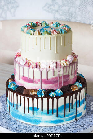 Three-tiered colored cake with colored smudges of chocolate on a light background. Picture for a menu or a confectionery catalog with copy space - Stock Photo