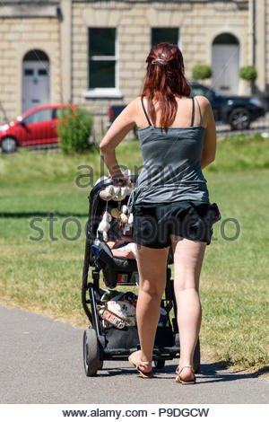 A woman pushes a baby in a buggy in Bath, Somerset, England, UK during the 2018 heatwave. - Stock Photo