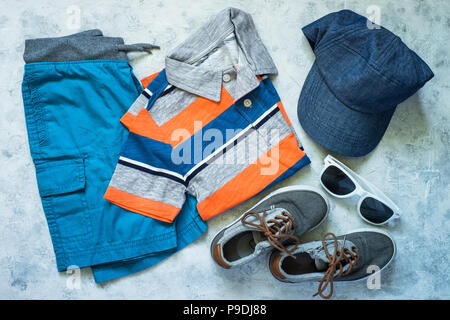 Child summer clothes - polo, shorts and cap top view on stone background. Fashion clothes set. Top view. - Stock Photo
