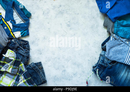 Child clothes - jeans, polo, shorts and shirt top view on stone background. Top view with copy space. - Stock Photo
