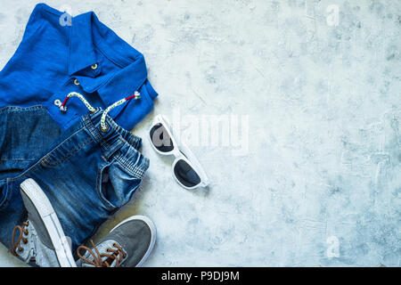 Child clothes - jeans, polo and sunglasses top view on stone background. Top view with copy space. - Stock Photo