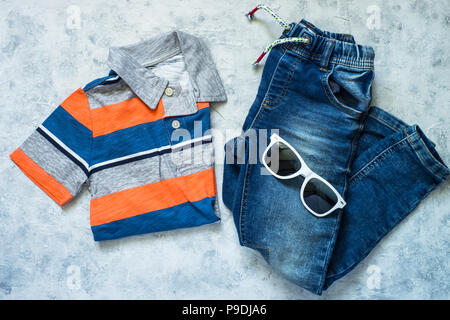 Child clothes - jeans, polo and sunglasses top view on stone background. Top view. - Stock Photo