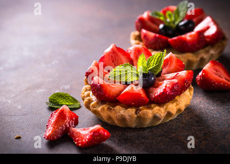 Strawberry tart with custard cream and fresh berries on dark rusty table. - Stock Photo