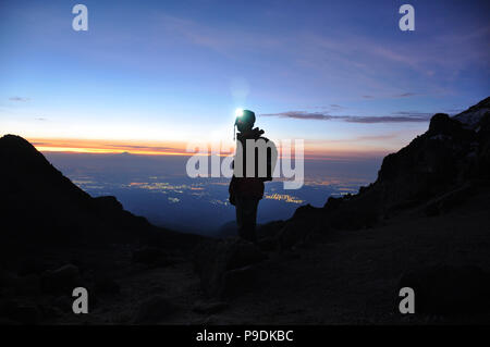 Silhouette of a Mountaineer standing on a Mountain in front of the Horizon with Headtorch on Mount Iztaccihuatl Volcano, Mexico - Stock Photo