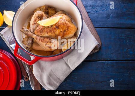 The whole chicken baked with lemon and rosemary in a red cast iron. Blue wooden background and gray towel. Knife and fork. Free space for text - Stock Photo