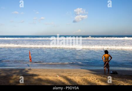 A surfer is looking at the sea shore to check the waves. Location : Kuta Beach in Bali, Indonesia. - Stock Photo