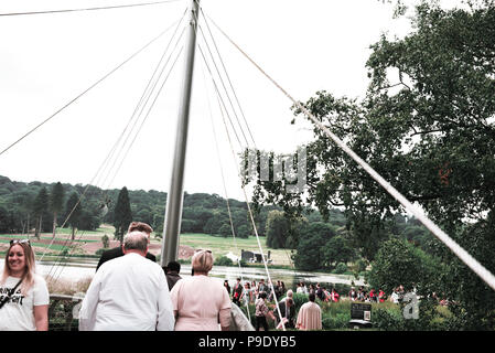 A crowd of people walking over a bridge for graduation with surrounding greenery in the background. - Stock Photo
