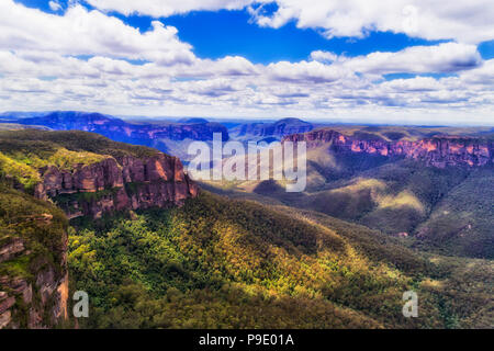Landmarking Pulpit rock in BLue Mountains national park of Australia on a sunny day with blue sky in aerial view over deep gum-tree covered creek betw - Stock Photo