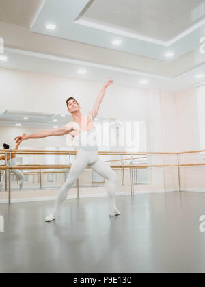 Young handsome male dancer practicing in classical ballet in small studio with mirrors. Man in white tights. Professional choreographer is working on creating performance. - Stock Photo