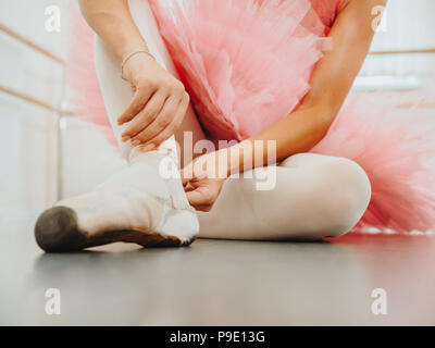 Young ballerina in pink tutu costume wraps white silk ribbons of soft top ballet shoes pointe and ties them up. Woman preparing for dance training lessons in gym. - Stock Photo