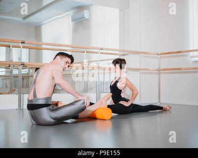 Preparation of body before performance in ballet studio. Male dancer and ballerina warming up near barre on rehearsal. - Stock Photo