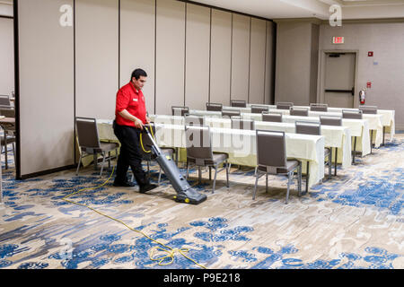 Orlando Florida Doubletree by Hilton Orlando SeaWorld hotel property grounds conference room interior housekeeping Hispanic man vacuuming carpet - Stock Photo