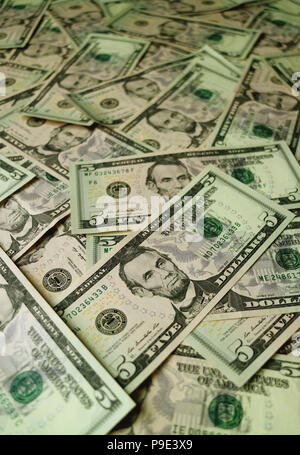 Heap of United States five dollar bills with selective focus and blurred background - Stock Photo