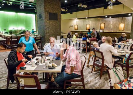 Orlando Florida Doubletree by Hilton Orlando SeaWorld hotel property grounds Laguna restaurant interior tables - Stock Photo