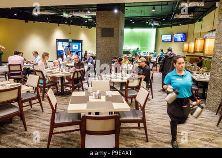 Orlando Florida Doubletree by Hilton Orlando SeaWorld hotel property grounds Laguna restaurant tables family Hispanic woman waitress interior - Stock Photo