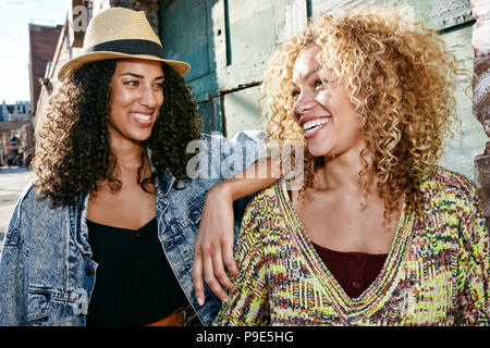 Portrait of two smiling young women with long curly black and blond hair, looking at each other. - Stock Photo