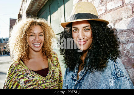Portrait of two smiling young women with long curly black and blond hair, looking at camera. - Stock Photo