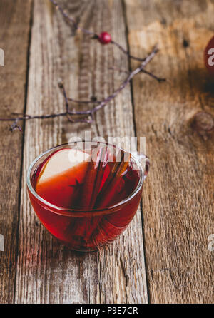 Hot drink with apple cider, cinnamon stick and sliced fruit in glass mugs on rustic wooden table - Stock Photo