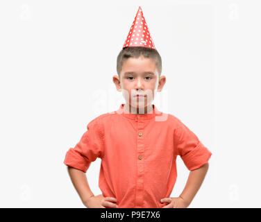 Dark haired little child wearing birthday cap with a confident expression on smart face thinking serious - Stock Photo