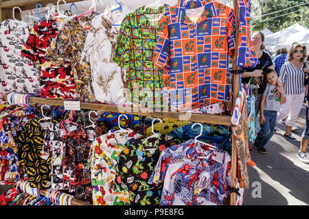 Florida Micanopy Fall Harvest Festival annual small town community event booths stalls vendors buying selling display sale men's theme shirts UF logo - Stock Photo