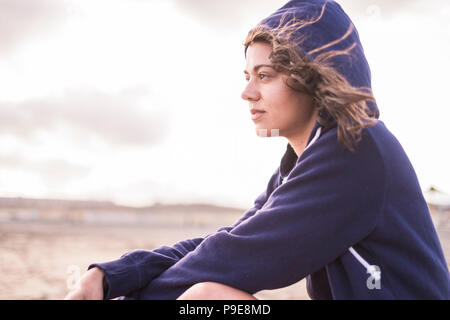 beautiful girl sitting at the beach outdoor in summer holiday.  lost in her thoughts with independence and freedom concept. bright sky with clouds in  - Stock Photo