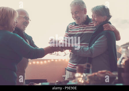 senior adult people group in leisure activity doing barbeque bbq on the rooftop terrace at home with mountain view. meal and wine for two men and two  - Stock Photo