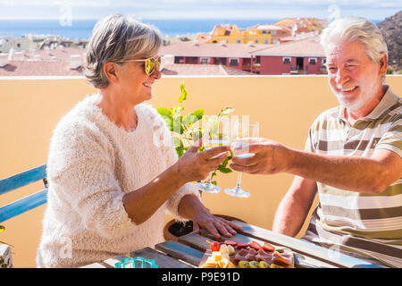 nice couple of retired adult stay together on the roofto pterrace eating and drinking some food and drink. happy smile people outdoor in great lifesty - Stock Photo