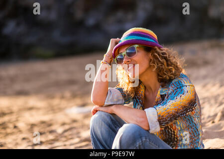 pretty blonde young woman sit down on the sand at the beach relaxing and enjoying sunset and sunny day of vacation. stay well in a natural place and o - Stock Photo