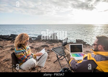 nice couple enjoying a sunset at the end of the day. travel lifestyle in wanderlust for happy cacucasian people. working alternative office with lapto - Stock Photo