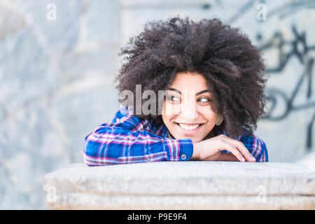 portrait of black skin african race of beautiful young girl smiling and looking at her side. enjoying the time and the leisure activity. casual and fa - Stock Photo