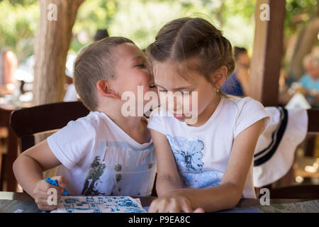 A little boy are whispering something to a pretty girl in a street restaurant. - Stock Photo
