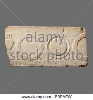 Marble relief fragment depicting athletic prizes, Mid-Imperial, Antonine, 2nd century A.D., Roman, Marble, H. 12 3/4 in. (32.5 cm); length 26 3/8 in. (67.7 cm), Stone Sculpture, On this dedicatory relief are representations of the standard prizes awarded at four venues in Greece: an amphora of olive oil from the Panathenaic games at Athens, a shield from the games at Argos, and two wreaths (of pine and celery) from the prestigious Panhellenic games at Isthmia and Nemea respectively. - Stock Photo