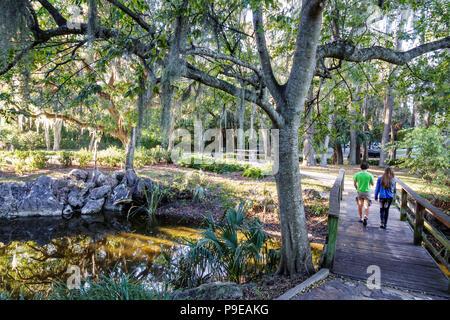 Gainesville Florida University of Florida campus Ficke Gardens student hiking trail walking path bridge Spanish moss-covered tree boy girl teen - Stock Photo