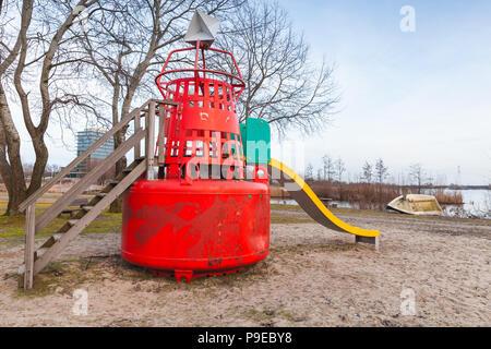 Slide made of red navigation buoy on public playground of Muiderzand marina, Amsterdam, Netherlands - Stock Photo