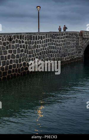 Two people walking across bridge, Castillo de San Gabriel, Arrecife, Lanzarote, Canary Islands, Spain - Stock Photo