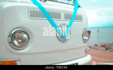 Volkswagen VW Badge on a camper van dressed in a blue wedding ribbon. - Stock Photo