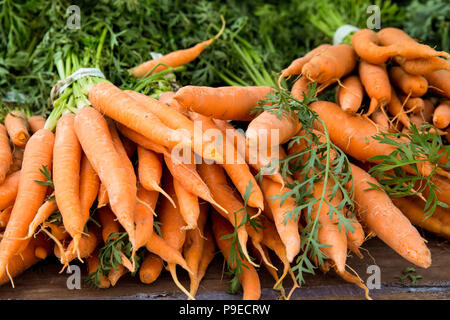 Crop of organically grown carrots on display at farmers market - Stock Photo